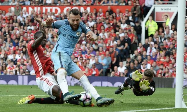 Manchester City's defender Nicolas Otamendi (C) attempts to shoot past Manchester United's defender Eric Bailly (L) goalkeeper David de Gea (R) on September 10, 2016 (AFP Photo/Oli Scarff)