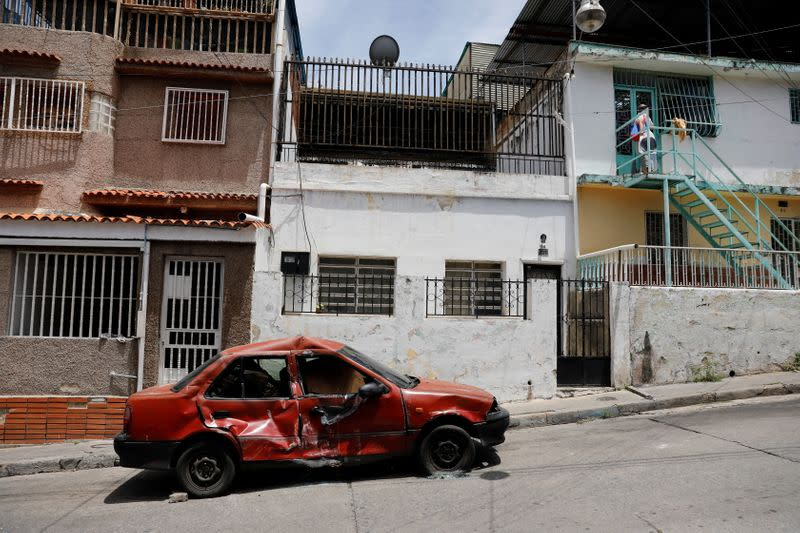 A car crushed by the Special Forces tank (FAES) is seen after armed confrontations between members of El Koki's criminal gang and police forces, in Caracas