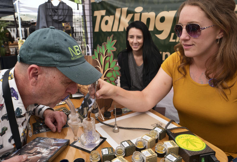 "FILE - In this Thursday, June 20, 2019 file photo a Mark ""Wiz"" Schulze, left, takes a puff of a cannabis concentrate from Talking Trees farm during a business to business networking event in Los Angeles. California is increasing business tax rates on legal marijuana, a move that stunned struggling companies that have been pleading with the state to do just the opposite. Hefty marijuana taxes that can approach 50 percent in some communities have been blamed for pushing shoppers into California's tax-free illegal market, which is thriving. Industry analysts estimate that $3 are spent in the illegal market for every $1 in the legal one. (AP Photo/Richard Vogel,File)"
