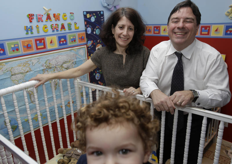 """In this Jan. 30, 2013 photo, Drew and Frances Pardus-Abbadessa pose for a picture with their son, Pavol, 1, in the nursery originally intended for a child they have been trying to adopt for five years, at their apartment in New York.  The boy's Russian name is Vladimir,  but they hope one day to be able to name him Franco Michael ,  the name still displayed on the wall. The Pardus-Abbadessa family were among a group initially known as the """"Kyrgyz 65"""" - Americans who were in the process of adopting 65 orphans from the Central Asian republic when it suspended international adoptions in 2008 due to allegations of fraud.  Some of the children were placed in domestic adoptions, and last summer nine of the remaining children finally were allowed to go to America. The Pardus-Abbadessas are now among 16 U.S. families still waiting. (AP Photo/Seth Wenig)"""