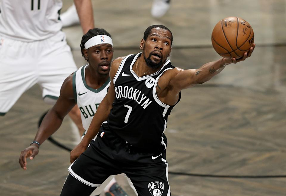 Kevin Durant #7 of the Brooklyn Nets grabs the loose ball as Jrue Holiday #21 of the Milwaukee Bucks defends in the first half during game seven of the Eastern Conference second round at Barclays Center on June 19, 2021 in the Brooklyn borough of  New York City. NOTE TO USER: User expressly acknowledges and agrees that, by downloading and or using this photograph, User is consenting to the terms and conditions of the Getty Images License Agreement. (Photo by Elsa/Getty Images)