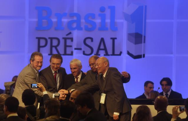 Brazil's Mines and Energy Minister Edison Lobao (2nd L) meets representatives of the consortium winner of the auction for the Libra offshore oilfield during a ceremony in Rio de Janeiro October 21, 2013. Brazil geared up on Monday to sell production rights to Libra, its largest-ever oil discovery, in a landmark auction that sparked widespread nationalist protests even though most of the world's premier energy companies opted to stay away. REUTERS/Ricardo Moraes (BRAZIL - Tags: POLITICS BUSINESS ENERGY)