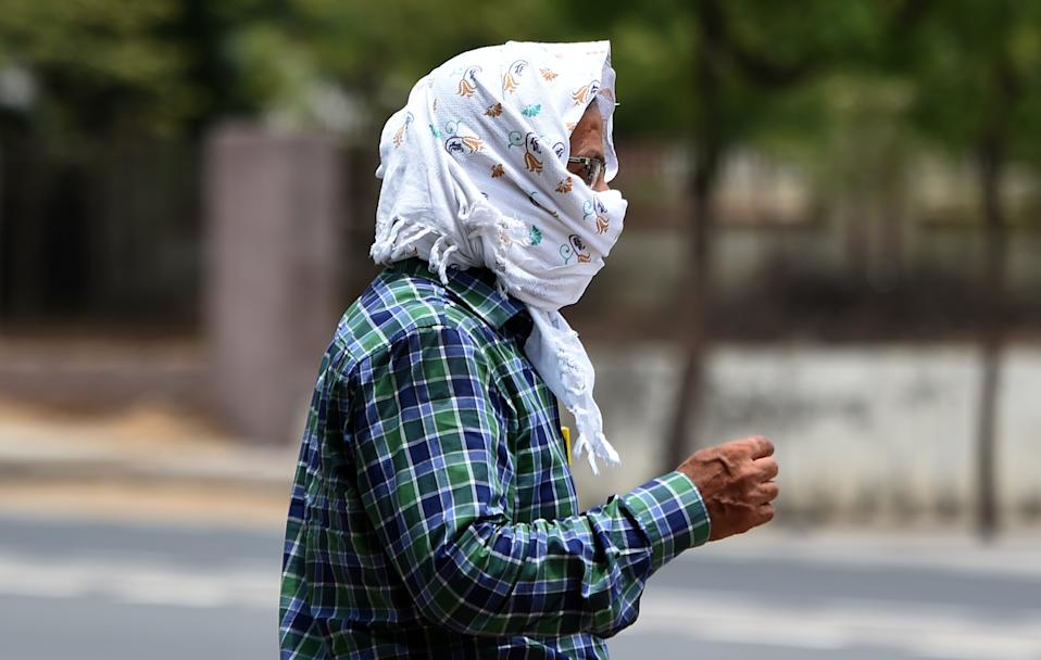An Indian man walks with his face covered to to protect himself from the heat during a hot day in Churu, in the Indian state of Rajasthan on June 4, 2019. - Temperatures in an Indian desert city hit 50 degrees Celsius (122 Fahrenheit) for the second time in three days as a deadly heatwave maintained its grip on the country. The thermometer hit 50.3 (122.54 Fahrenheit) in Churu in Rajasthan state, sending residents scrambling for shade to escape the searing sun. (Photo by Money SHARMA / AFP) (Photo credit should read MONEY SHARMA/AFP/Getty Images)