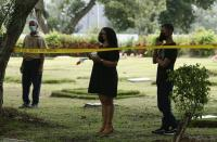 Brenda Bethancourt, the daughter of Lt. Braulio Bethancourt, watches as forensic workers exhume what are believed to be the remains of her father, a victim of the 1989 U.S. invasion, at the Jardin de Paz cemetery in Panama City, Thursday, April 15, 2021. The prosecutor's office has begun an exhumation of human remains at the Panamanian cemetery in a renewed attempt to confirm the identities of the victims of the U.S. invasion. (AP Photo/Arnulfo Franco)