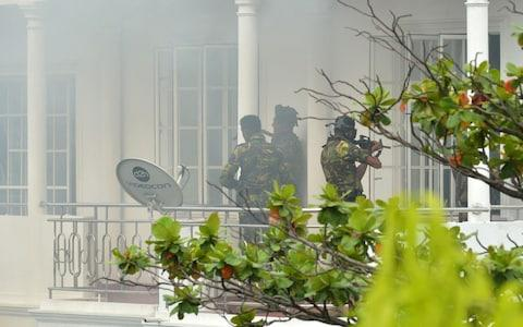 Sri Lankan Special Task Force (STF) personnel are pictured outside a house during a raid - Credit: ISHARA S. KODIKARA/AFP