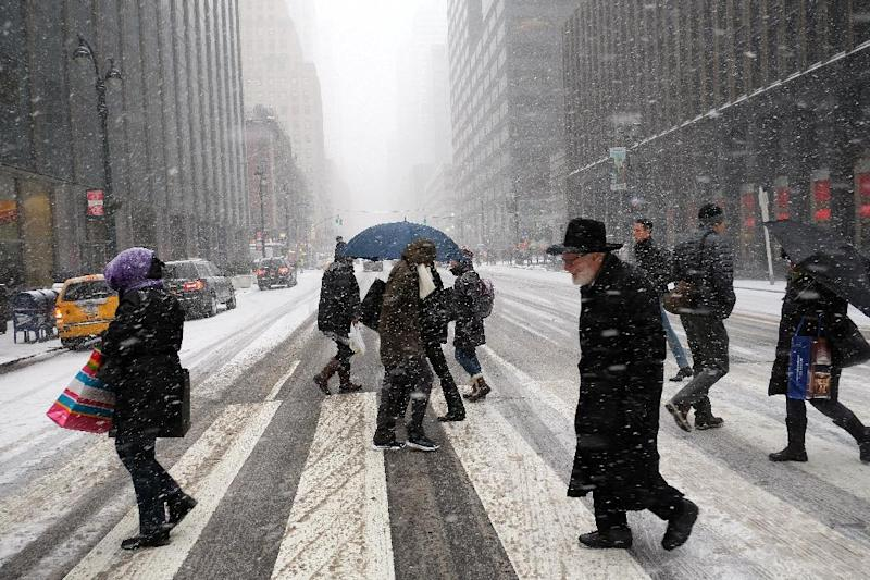 People cross a city street in a snow storm in New York on January 26, 2015 (AFP Photo/Jewel Samad)