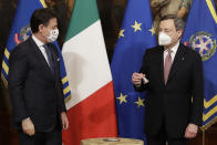 Italian outgoing Premier Giuseppe Conte handed over the cabinet minister bell to new Premier Mario Draghi, during the handover ceremony at Chigi Palace Premier's office, in Rome, Saturday, Feb. 13, 2021. (AP Photo/Andrew Medichini)