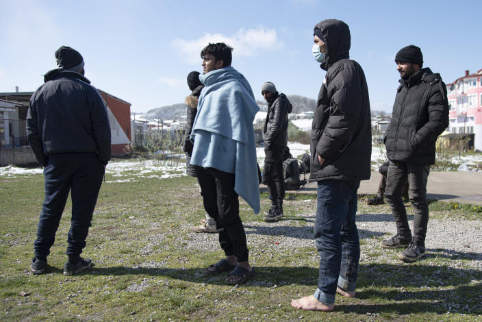 Migrants stand outside the Miral camp, in Velika Kladusa, Bosnia, Wednesday, April 7, 2021. Bosnia is seeing a rise in coronavirus infections among migrants and refugees living in its camps, as it struggles to cope with one of the Balkans' highest COVID-19 death and infection rates among the general population.(AP Photo/Davor Midzic)