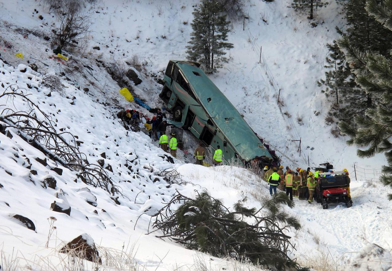 Emergency personnel respond to the scene of a multiple-fatality accident where a tour bus careened through a guardrail along an icy highway and several hundred feet down a steep embankment, authorities said, Sunday, Dec. 30, 2012 about 15 miles east of Pendleton, Ore. The charter bus carrying about 40 people lost control around 10:30 a.m. on the snow- and ice-covered lanes of Interstate 84, according to the Oregon State Police. (AP Photo/East Oregonian, Tim Trainor)