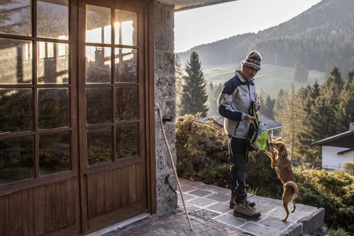 """In this image taken on Thursday, April 23, 2020, alpine guide Ernesto Cocchetti, 57, prepares to go walking outside his house in Castione Della Presolana, near Bergamo, northern Italy. Cocchetti predicts a return to """"living with nature's rhythms"""" once government restrictions to prevent the spread of COVID-19 will be eased. (AP Photo/Luca Bruno)"""