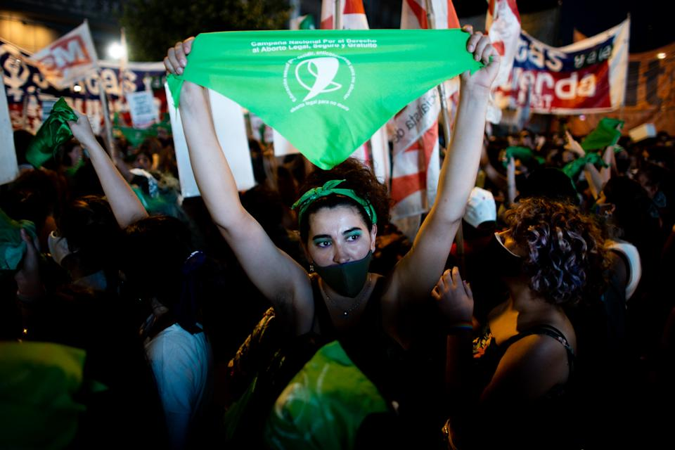 BUENOS AIRES, ARGENTINA - DECEMBER 10: A pro-choice activist holds a green kerchief while waiting outside the National Congress as Deputies vote on a bill to legalize abortion on December 10, 2020 in Buenos Aires, Argentina. The bill authorizes legal, voluntary and free interruption of pregnancy until the 14th week while allowing doctor's conscientious objection. If approved, the bill will be voted in the Senate in December 2020. It is the ninth bill to legalize abortion treated by the Argentine Congress and the first one publicly supported by the president of the country. (Photo by Tomas Cuesta/Getty Images)