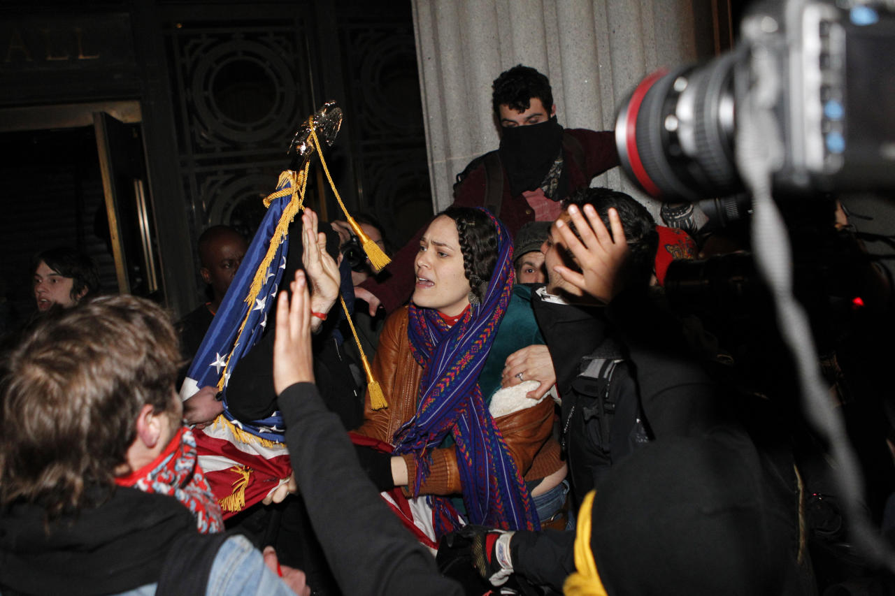 A woman pleads with Occupy Oakland protestors to not burn an American flag found inside Oakland City Hall during an Occupy Oakland protest, Saturday, January 28, 2012, in Oakland, Calif. Police were in the process of arresting about 100 Occupy protesters for failing to disperse Saturday night, hours after officers used tear gas on a rowdy group of demonstrators who threw rocks and flares at them and tore down fences. (AP Photo/Beck Diefenbach)