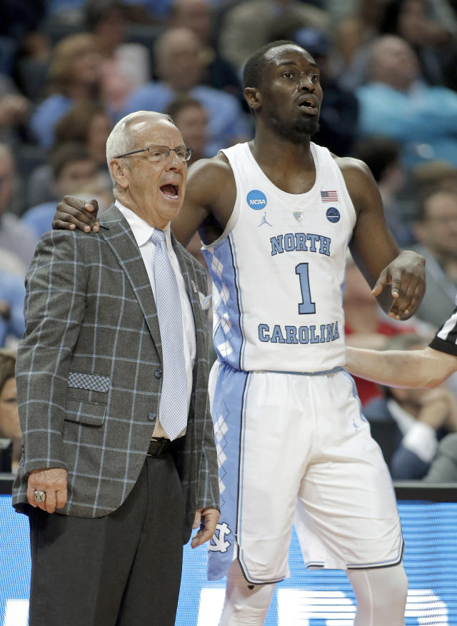 North Carolina's Theo Pinson (1) leans onto North Carolina head coach Roy Williams during the second half of a first-round game against Lipscomb in the NCAA men's college basketball tournament in Charlotte, N.C., Friday, March 16, 2018. (AP Photo/Bob Leverone)