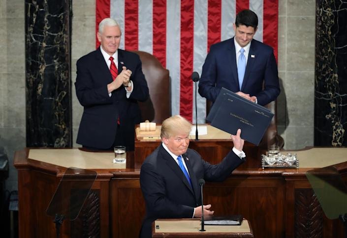 WASHINGTON, DC – JANUARY 30: U.S. President Donald J. Trump (C) holds up his speech as U.S. Vice President Mike Pence (L) and Speaker of the House U.S. Rep. Paul Ryan (R-WI) (R) look on during the State of the Union address in the chamber of the U.S. House of Representatives January 30, 2018 in Washington, DC. This is the first State of the Union address given by U.S. President Donald Trump and his second joint-session address to Congress. (Photo by Chip Somodevilla/Getty Images)