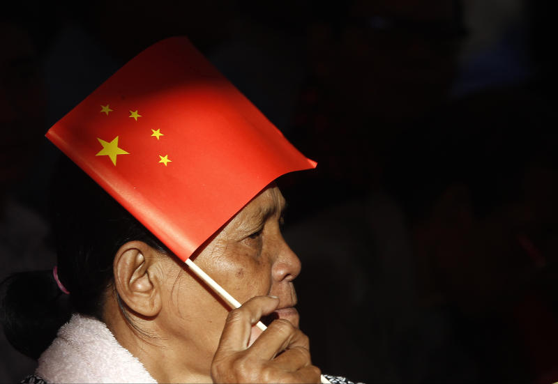 FILE - In this July 2, 2018 file photo, a woman uses a Chinese national flag to protect herself from the sun as she listens to Prime Minister Hun Sen who delivering his speech during an inauguration ceremony of a sky bridge funded by China for its official use in Phnom Penh, Cambodia. A California-based security-research firm said Wednesday, July 11, 2018, that it found evidence that an elite Chinese government-linked hacking team has penetrated computer systems belonging to Cambodia's election commission, opposition leaders and media in the months leading up to Cambodia's July 29 election. (AP Photo/Heng Sinith, File)