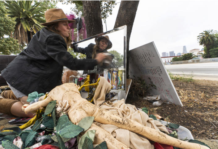 """Dawn Woodward, 39, who is homeless and originally from Arizona, dusts a mirror set outdoors in a homeless camp on the side of the CA-101 highway in the Echo Park neighborhood in Los Angeles Tuesday, May 11, 2021. California Gov. Gavin Newsom on Tuesday proposed $12 billion in new funding to get more people experiencing homelessness in the state into housing and to """"functionally end family homelessness"""" within five years. (AP Photo/Damian Dovarganes)"""
