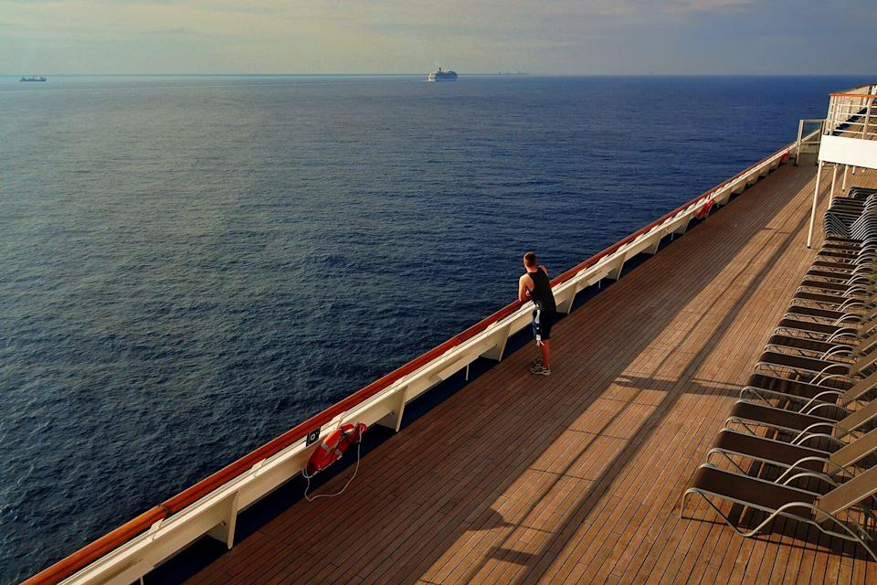 A man looks over the sea from the top deck of a cruise ship off the coast of the island of Cozumel, Mexico