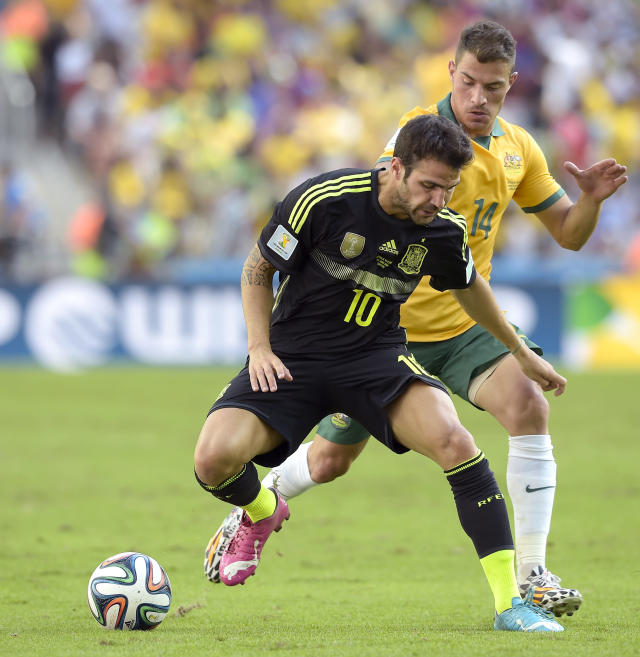 Spain's Cesc Fabregas controls the ball next to Australia's James Troisi during the group B World Cup soccer match between Australia and Spain at the Arena da Baixada in Curitiba, Brazil, Monday, June 23, 2014. (AP Photo/Manu Fernandez)