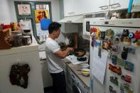 Fitness trainer Mike Lee demonstrates making a dish with plant-based meat Omnipork for the camera at his home in Hong Kong