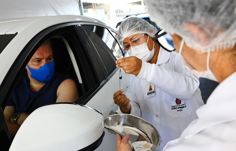 SAO PAULO, BRAZIL - MAY 21: A driver waits to receive a dose of the AstraZeneca COVID-19 vaccine from a public health worker at a drive-through vaccination post on May 21, 2021 in Sao Paulo, Brazil. Around 20 percent of Brazilians have received their first vaccination dose. Health experts are warning that Brazil should brace for a new surge of COVID-19 amid a slow vaccine rollout and relaxed restrictions. The state of Sao Paulo has registered over 3 million cases of COVID-19 and more than 100,000 deaths. Over 440,000 people have been killed in Brazil by COVID-19, second only to the U.S. (Photo by Mario Tama/Getty Images)