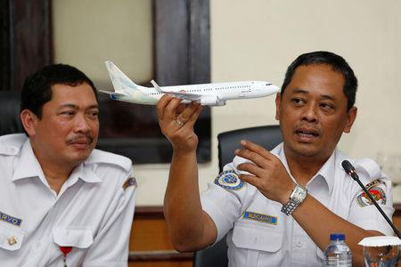 Indonesia's National Transportation Safety Committee (KNKT) sub-committee head for air accidents, Nurcahyo Utomo, holds a model airplane while speaking during a news conference on its investigation into a Lion Air plane crash last month, in Jakarta