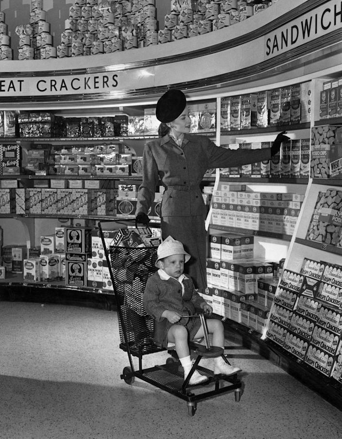 <p>A stylish woman peruses through the cracker aisle as her young son sits in the front of the grocery cart stroller. </p>