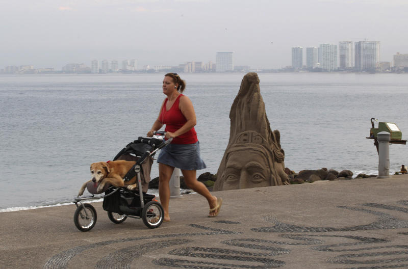 A woman pushes her dog in a baby stroller along the beach in the resort city of Puerto Vallarta, Mexico, Friday, May 25, 2012. Hurricane Bud lost a little of its sting early Friday, but remained a potent Category 2 storm as it headed toward a string of laid-back beach resorts and small mountain villages on Mexico's Pacific coast south of Puerto Vallarta.  (AP Photo/Bruno Gonzalez)