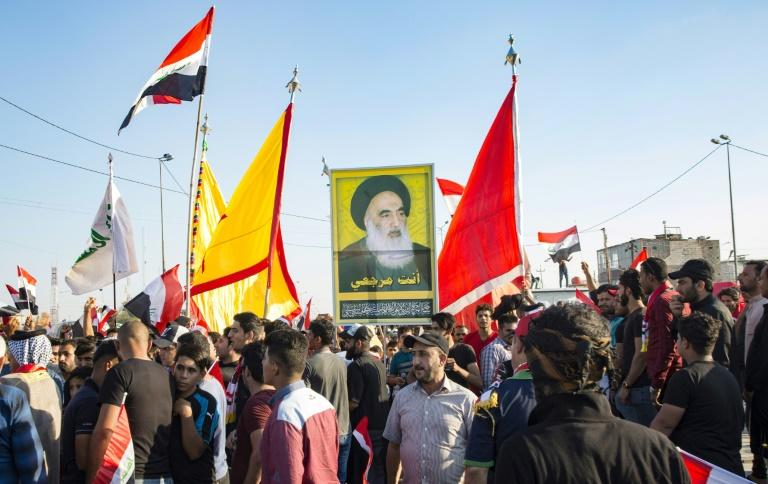 Demonstrators in Iraq's main southern city of Basra hold aloft a portrait of Shiite spiritual leader Grand Ayatollah Ali Sistani, who has increasingly backed their cause