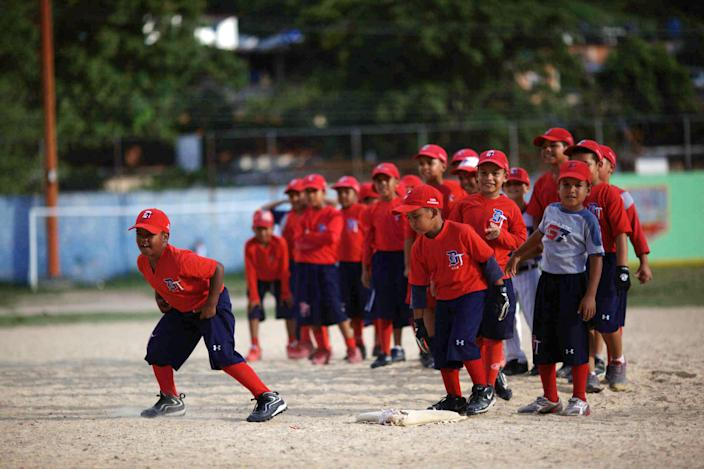 In this Oct. 25, 2012 photo, boys train at a baseball school in Maracay, Venezuela. Many of the boys are inspired by the example of Detroit Tigers slugger Miguel Cabrera, who learned the game on this very field. Their baseball school in the poor neighborhood where Cabrera grew up is one of many across Venezuela, a web for training young ballplayers that has made the country a powerhouse in the U.S. major leagues. (AP Photo/Ariana Cubillos)