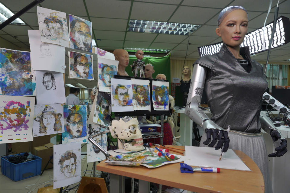 Sophia's artworks are displayed at Hanson Robotics studio in Hong Kong on March 29, 2021. Sophia is a robot of many talents — she speaks, jokes, sings and even makes art. In March, she caused a stir in the art world when a digital work she created as part of a collaboration was sold at an auction for $688,888 in the form of a non-fungible token (NFT). (AP Photo/Vincent Yu)