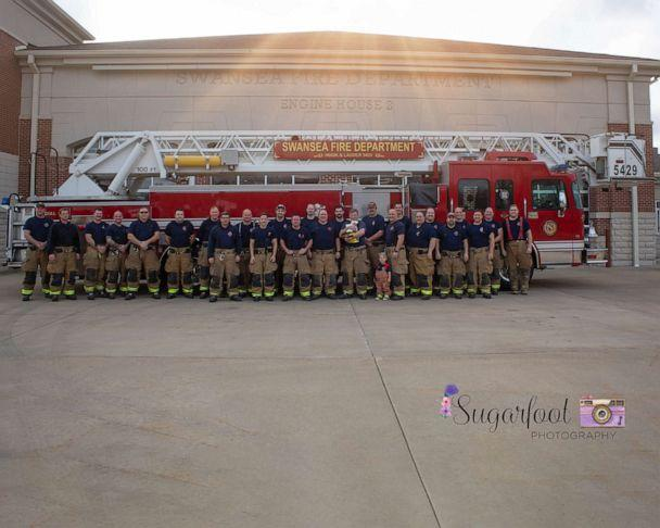 PHOTO: Baby Brett photographed with her late father's colleagues at the Swansea firehouse. (Sugarfoot Photography)