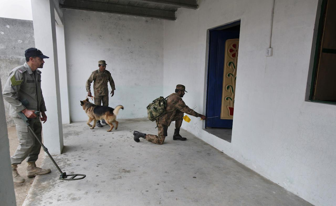 In this Wednesday, Jan. 8, 2014, photo, Pakistani soldiers search a model house during a training session at the Counter IED Explosives and Munitions School in Risalpur, Pakistan. Militants in Pakistan have become devilishly ingenious about where they plant improvised explosive devices, a type of bomb responsible for thousands of wounds and deaths in Pakistan. They've been found strapped to children's bicycles, hidden inside water jugs and even hung in tree branches. (AP Photo/Anjum Naveed)