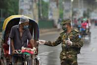 Bangladesh army personnel question a man commuting on a rickshaw at a checkpoint in Dhaka