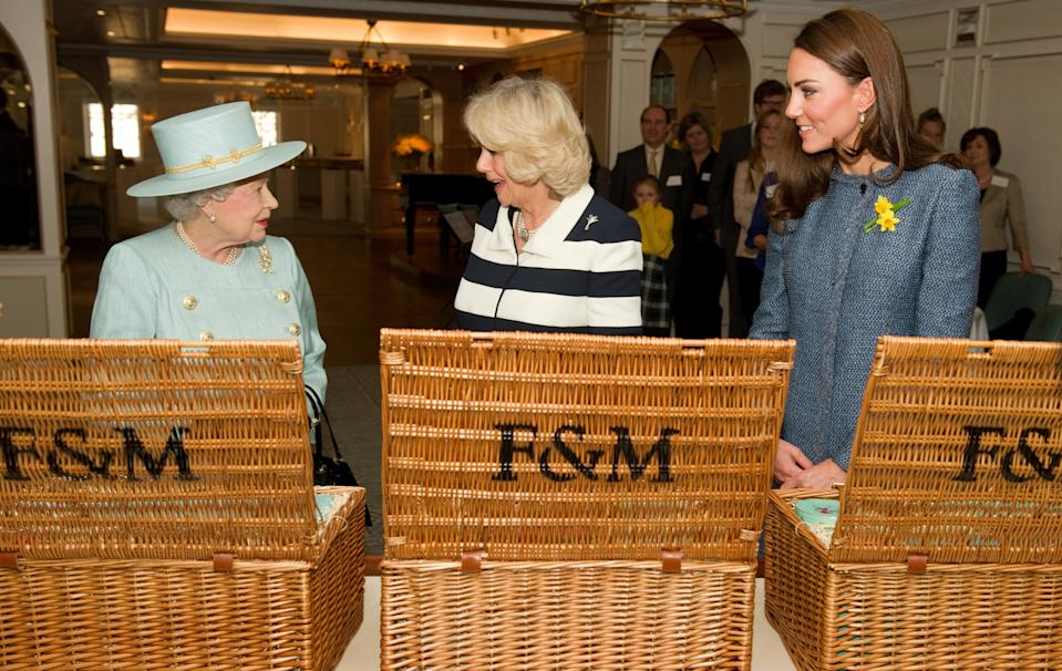 Britain's Queen Elizabeth, Camilla, Duchess of Cornwall and Catherine, Duchess of Cambridge (L-R) look at their hampers after being presented with gifts at the Fortnum and Mason food store in London March 1, 2012. REUTERS/Leon Neal/POOL  (BRITAIN - Tags: ROYALS ENTERTAINMENT BUSINESS FOOD)