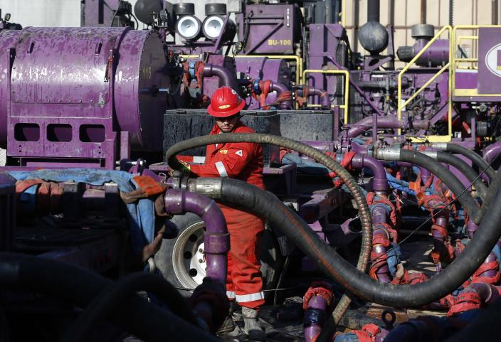 A worker adjusts hoses at a hydraulic fracturing operation near Mead, Colo. (Photo: Brennan Linsley/AP)