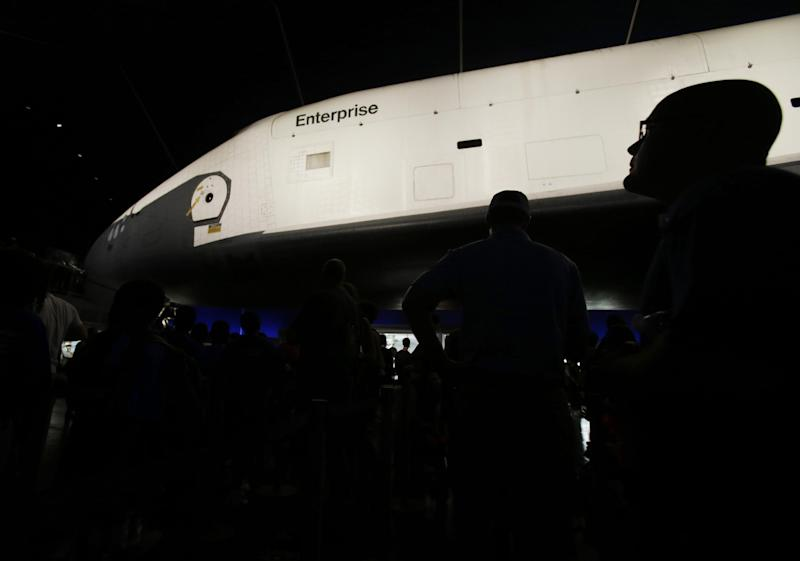 Visitors look at the space shuttle Enterprise in its newly completed pavilion on the deck of the Intrepid Sea, Air & Space Museum in New York, Wednesday, July 10, 2013. With a ribbon-cutting ceremony the pioneering shuttle has been restored from the damages it incurred during Superstorm Sandy. (AP Photo/Seth Wenig)