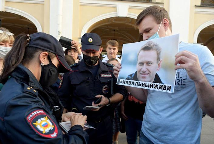 """Police officers check documents of a man standing with a placard with an image of Alexei Navalny during a gathering to express support for the opposition leader after he was rushed to intensive care in Siberia suffering from a a suspected poisoning, in St. Petersburg on August 20, 2020.<span class=""""copyright"""">Olga Maltseva—AFP/Getty Images</span>"""