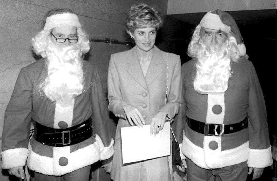 <p>Princess Diana attends a lunch with author and politician, Lord Jeffrey Archer and former Chancellor of the Exchequer, Lord Denis Healey, both dressed as Santa Claus.</p>