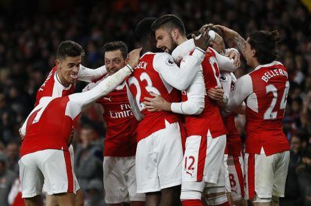 Arsenal's players celebrate after Leicester City's Robert Huth scores an own goal and the first goal for Arsenal