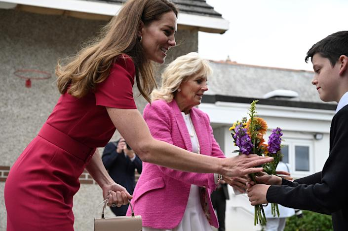 Britain's Catherine, Duchess of Cambridge, and First Lady Jill Biden receive flowers from students at Connor Downs Academy in Hayle, Cornwall on the sidelines of the G7 summit on June 11, 2021.