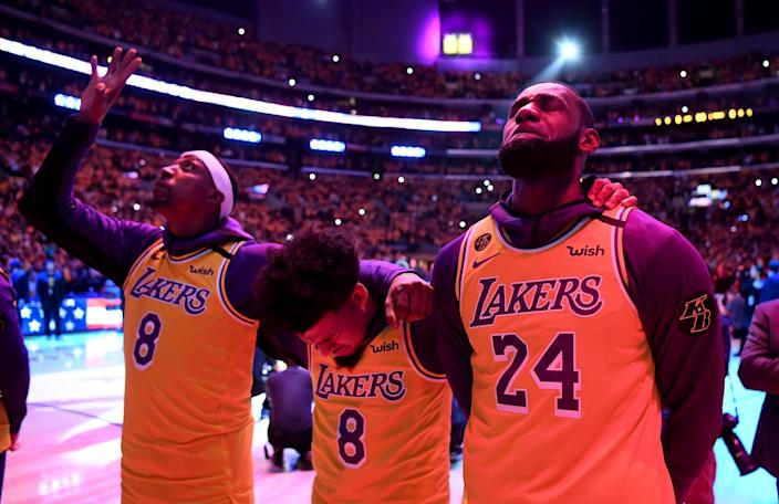 Lakers players, eyes closed or looking to the sky, wear jerseys with Kobe's numbers on the court in Staples Center.