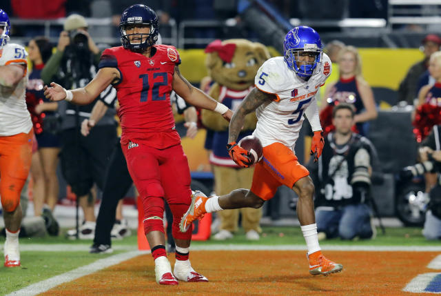 Boise State cornerback Donte Deayon (5) scores a touchdown after an interception as Arizona quarterback Anu Solomon (12) looks on during the second half of the Fiesta Bowl NCAA college football game, Wednesday, Dec. 31, 2014, in Glendale, Ariz. (AP Photo/Rick Scuteri)