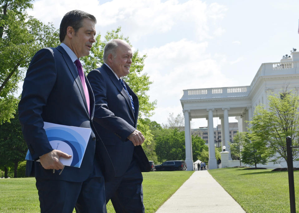 FILE - In this May 11, 2018, file photo, Association of Global Automakers President and Chief Executive Officer John Bozzella, left, and Ford Motor Company Chief Executive Officer Jim Hackett, right, arrive for a meeting with President Donald Trump at the White House in Washington. At a board meeting Tuesday, Dec. 1, 2020, the Alliance for Automotive Innovation, a big industry trade association, recognized that change is coming. Alliance CEO John Bozzella said automakers are committed to working with the Biden administration, which will renew the fight against climate change and likely will undo pollution and gas mileage rollbacks made by President Donald Trump. (AP Photo/Susan Walsh, File)