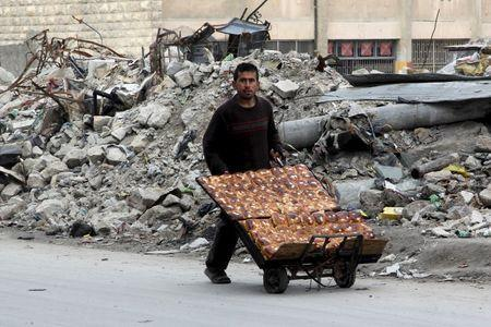 A man selling pastries walks past the rubble of damaged buildings in the rebel held al-Shaar neighborhood of Aleppo, Syria, February 10, 2016. REUTERS/Abdalrhman Ismail