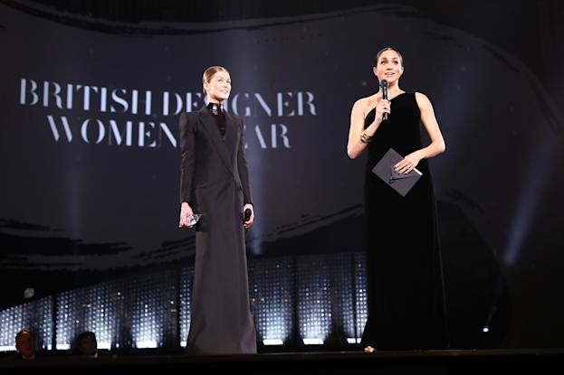 LONDON, ENGLAND - DECEMBER 10: Meghan, Duchess of Sussex and Rosamund Pike on stage to present the British Designer of the Year Womenswear Award during The Fashion Awards 2018 In Partnership With Swarovski at Royal Albert Hall on December 10, 2018 in London, England. (Photo by Tristan Fewings/BFC/Getty Images)