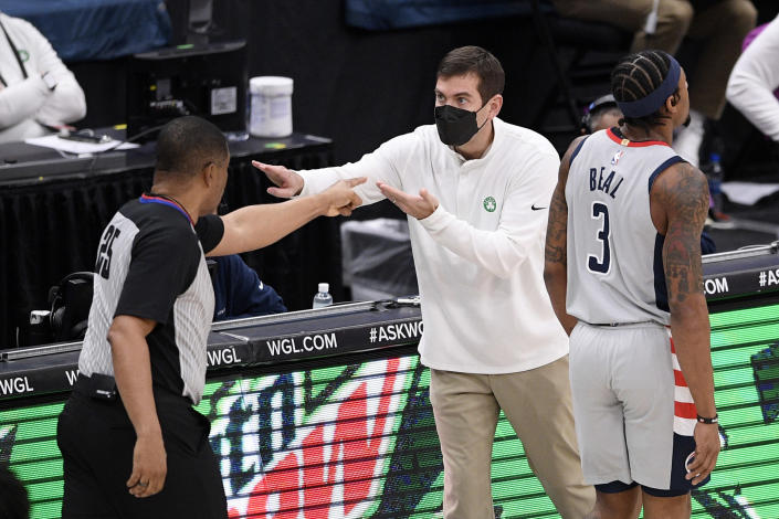 Boston Celtics head coach Brad Stevens, center, gestures next to referee Tony Brothers (25) during the first half of an NBA basketball game as Washington Wizards guard Bradley Beal (3) walks by, Sunday, Feb. 14, 2021, in Washington. (AP Photo/Nick Wass)