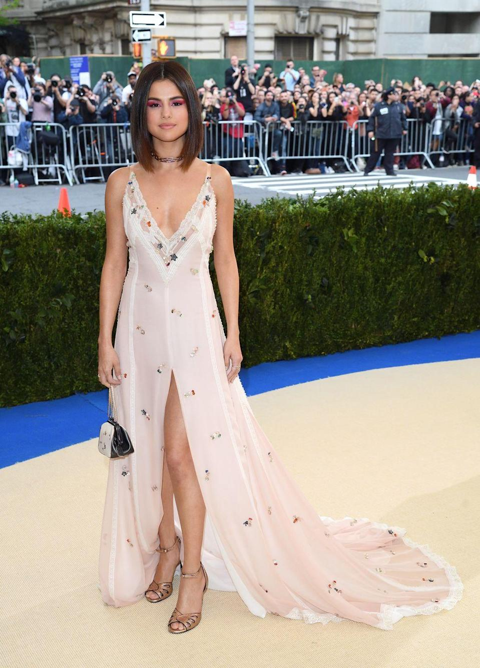 <p>Selena Gomez arrived, with The Weeknd on her arm, in this dusty pink Coach dress to the Met Gala 2017.</p>