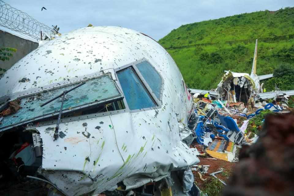 Officials inspect the wreckage of an Air India Express jet at Calicut International Airport in Karipur, Kerala, on August 8, 2020. - Fierce rain and winds lashed a plane carrying 190 people before it crash-landed and tore in two at an airport in southern India, killing at least 19 people and injuring scores more, officials said on August 8. (Photo by Arunchandra BOSE / AFP) (Photo by ARUNCHANDRA BOSE/AFP via Getty Images)