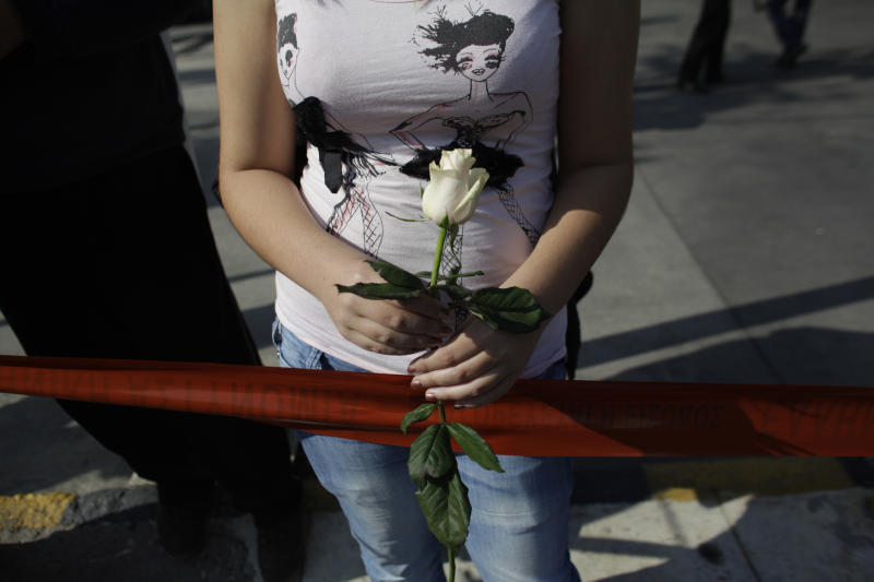 A supporter of the extreme right party Golden Dawn holds a flower in front of the party's office in northern Athens, Saturday, Nov. 2, 2013. Police looking for clues to the Friday evening murder of two members of the far-right Golden Dawn party and the grievous injury to a third say the gun used in the attack has not been used in previous terrorist attacks. (AP Photo/Kostas Tsironis)