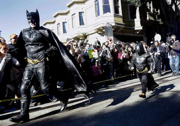 PHOTO: Miles Scott, dressed as Batkid, right, runs with Batman after saving a damsel in distress in San Francisco, Nov. 15, 2013. (Jeff Chiu/AP,FILE)